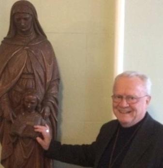 Mgr Yvon-Joseph Moreau, évêque de Ste-Anne de la Pocatière devant la statue de sainte Anne au Séminaire de Québec (Crédits photo : H. Giguère)