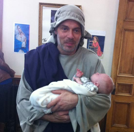 Image d'un jeune père de famille jouant saint Joseph avec Jésus dans ses bras (Crédits photo : H. Giguère)