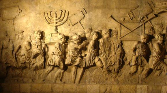 Arc de Triomphe de Titus sur la destruction de Jérusalem en l'an 70 montrant la prise de la Menorah par les romains (Crédit photo : copie au Beth Hatefutsoth reproduite via Wikimedia Commons)
