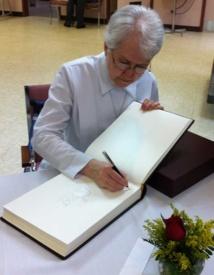 La prieure générale, soeur Raymonde Dussault, signe le Livre d'or des fêtes du 350e anniversaire de fondation du Séminaire de Québec (Photo H. Giguère)