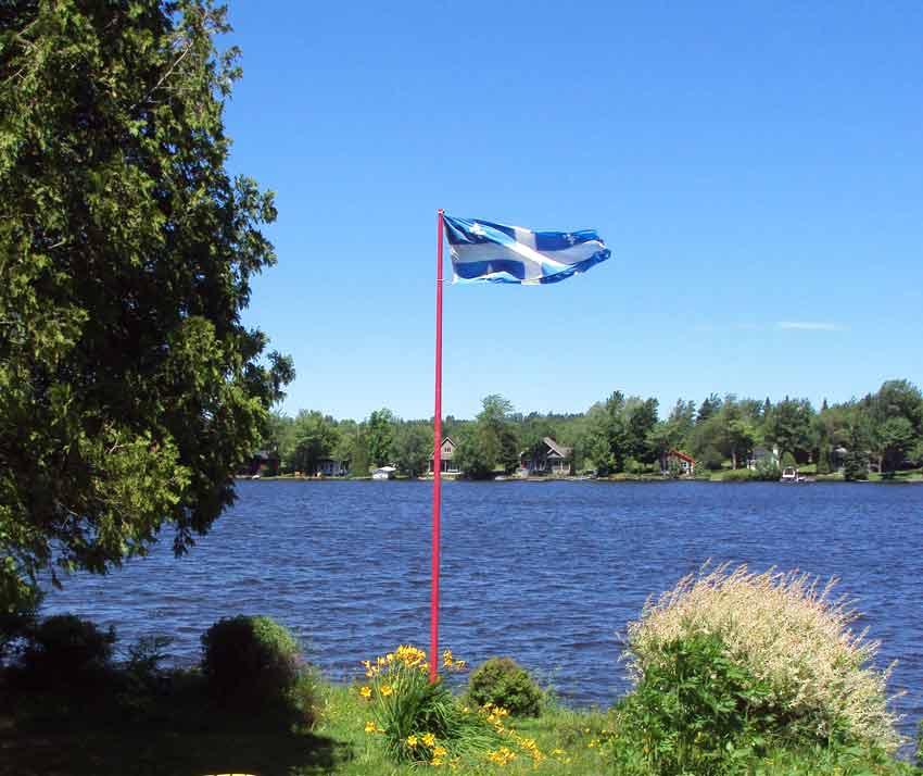 Le drapeau du Québec : croix blanche sur fond bleu avec quatre fleurs de lys (Crédits photo : H. Giguère)